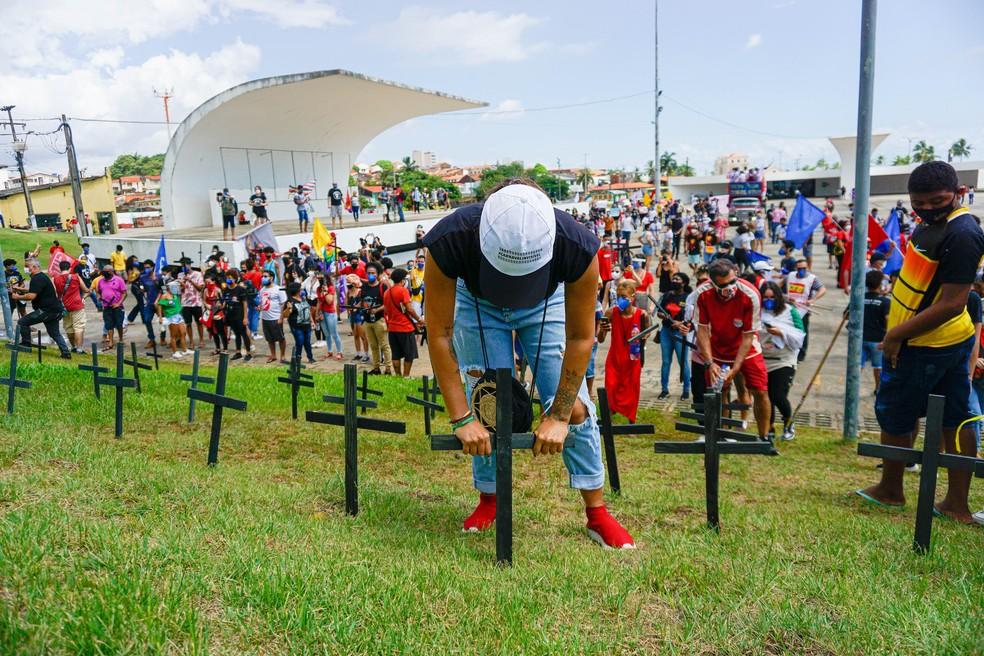 Manifestante coloca cruz no gramado da Praça Maria Aragão, em alusão aos mortos pela Covid-19 — Foto: Lucas Souza