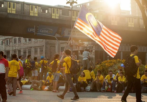 Manifestantes carregam bandeira da Malásia, em protesto na capital do país  (Foto: Charles Pertwee/Getty Images)