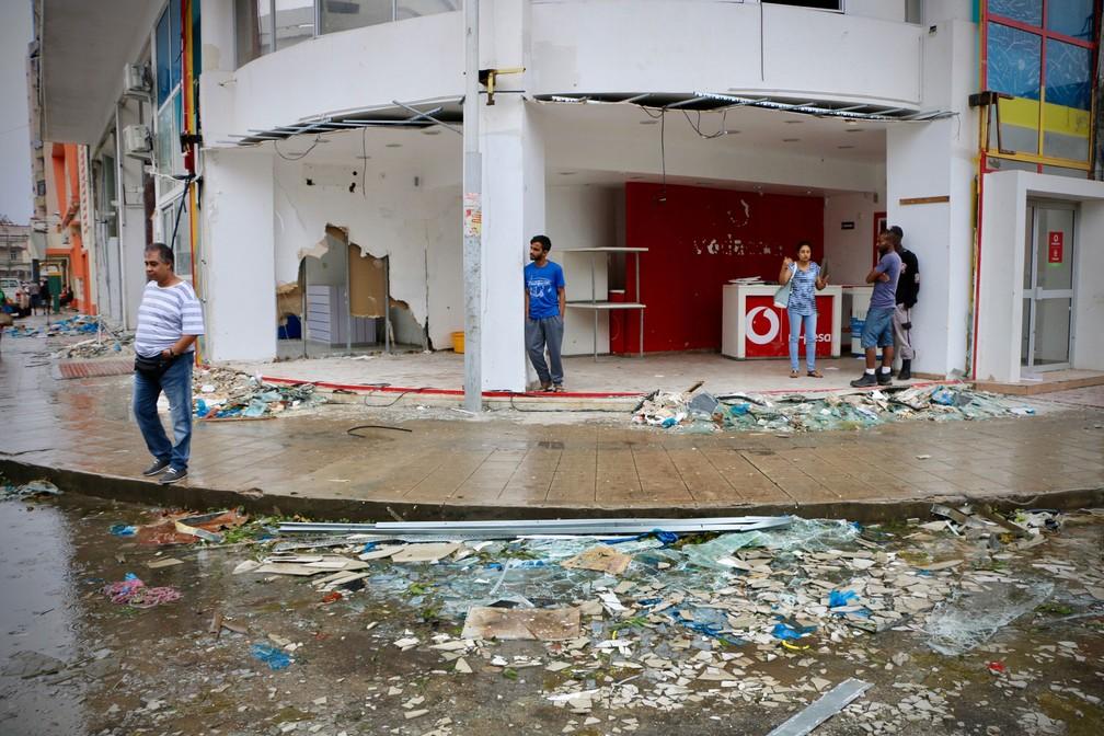 Moradores e lojistas são vistos em meio à destruição provocada pela passagem do ciclone Idai em Beira, Moçambique, no domingo (17)  — Foto: Adrien Barbier/AFP