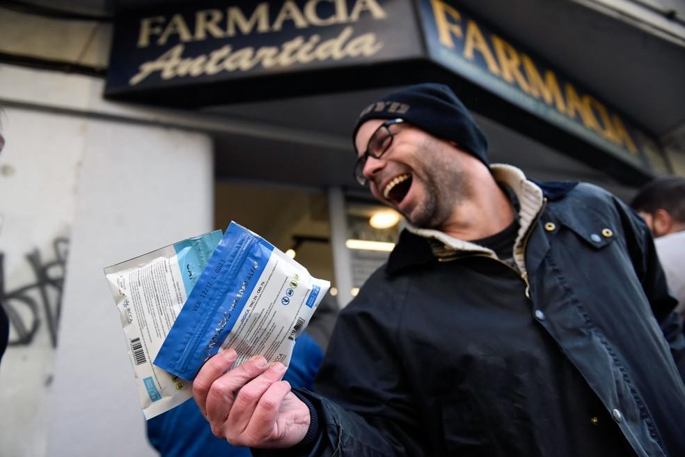 Juan Zas exibe dois pacotes de maconha legal comprados em uma farmácia do centro de Montevidéu. (Foto: Matilde Campodonico/AP)