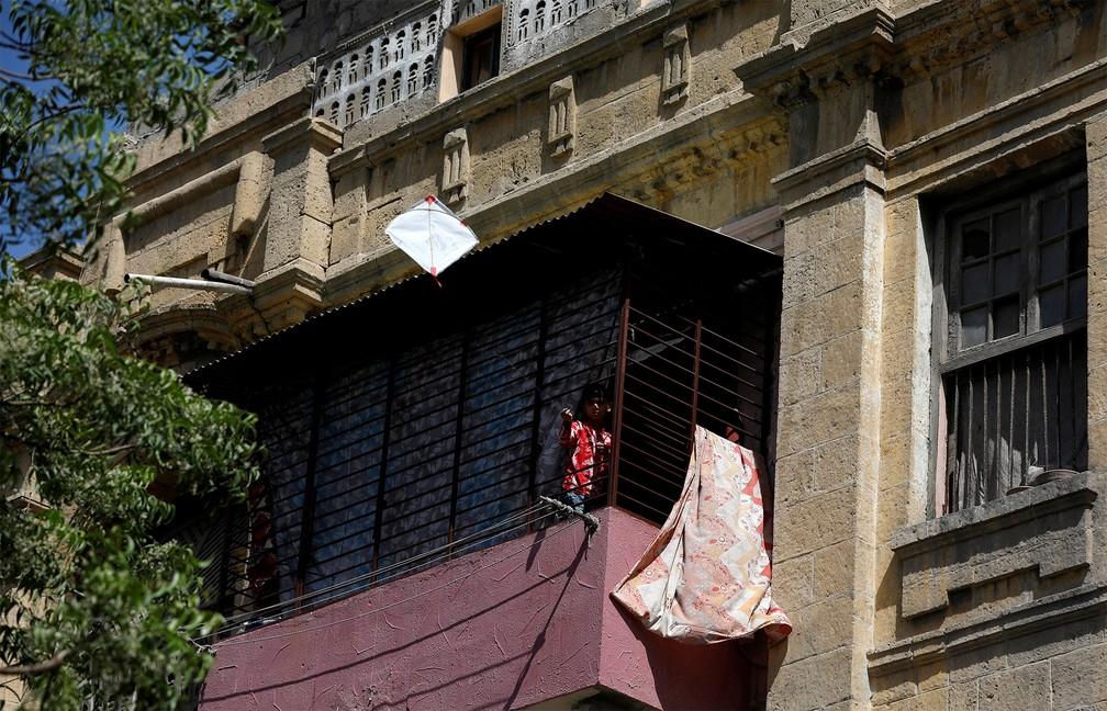 1º de abril - Menino empina uma pipa da janela de seu apartamento durante a quarentena em Karachi, no Paquistão — Foto: Akhtar Soomro/Reuters