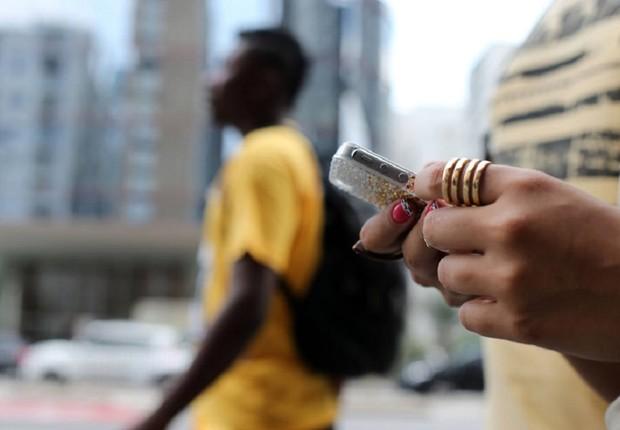 Mulher envia mensagem de celular no meio da rua ; hábitos do brasileiro em relação a celular ; cresce número de brasileiros ligados na internet mobile ; smartphone ;  (Foto: Tiago Queiroz/Estadão Conteúdo)