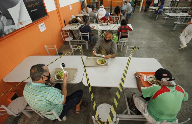 NITEROI, BRAZIL - AUGUST 05: People eat their meals while maintaining social distance at a popular soup kitchen on August 5, 2020 in Niteroi, Brazil. Employees received special training to ensure the safety of visitors. The site will intensify the cleanin (Foto: Getty Images)