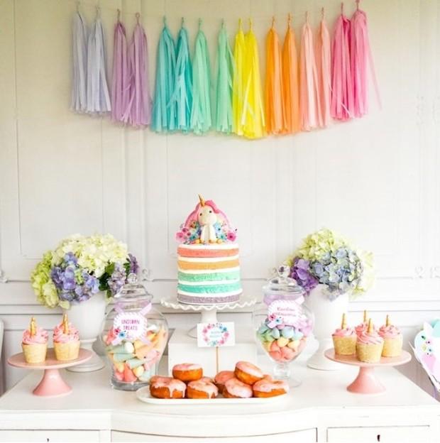 Os pompons decoram a mesa do bolo, mas também imitam a calda dos unicórnios. Unindo cada unidade a um barbante, ele pode fazer parte da fantasia das crianças (Foto: Pinterest/ Reprodução)