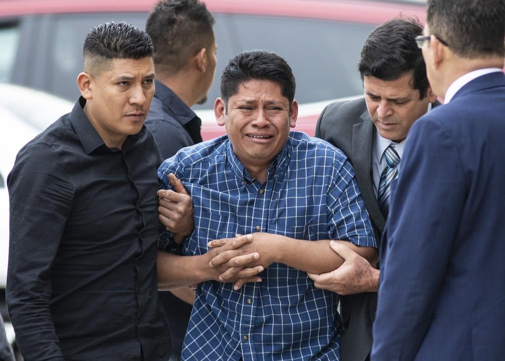 O pai de Marlen, Arnulfo Ochoa, cercado por parentes enquanto ia identificar o corpo da filha nesta quinta-feira (16). — Foto: Ashlee Rezin/Chicago Sun-Times via AP