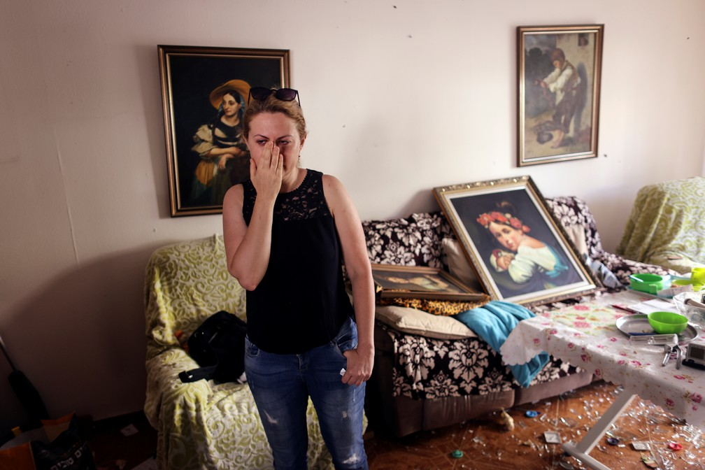 Sveta Shtilrman é vista na sala de estar de sua casa após seu prédio ser danificado por um ataque com foguete de Gaza em Ashdod, Israel, no domingo (17)   — Foto: Ronen Zvulun/Reuters