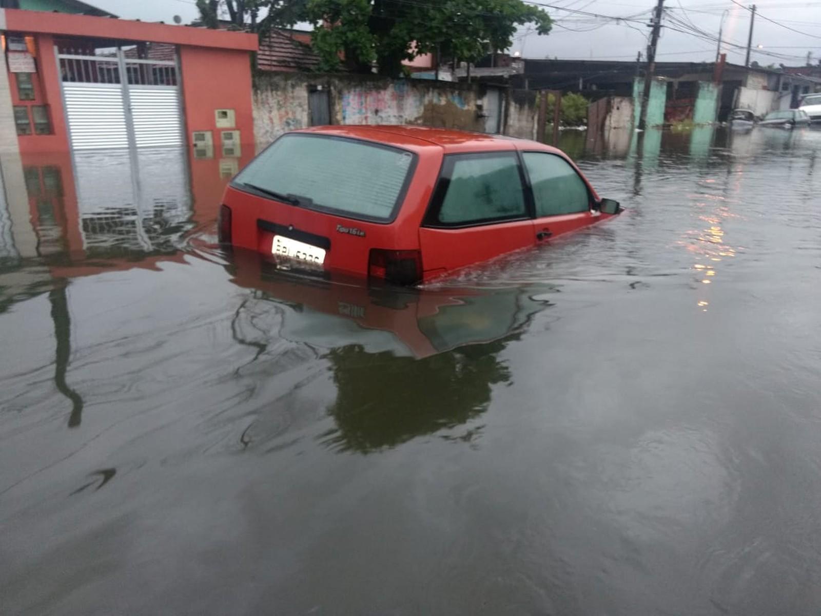 Carro é coberto pela água no bairro Jóquei Clube, em São Vicente — Foto: G1 Santos