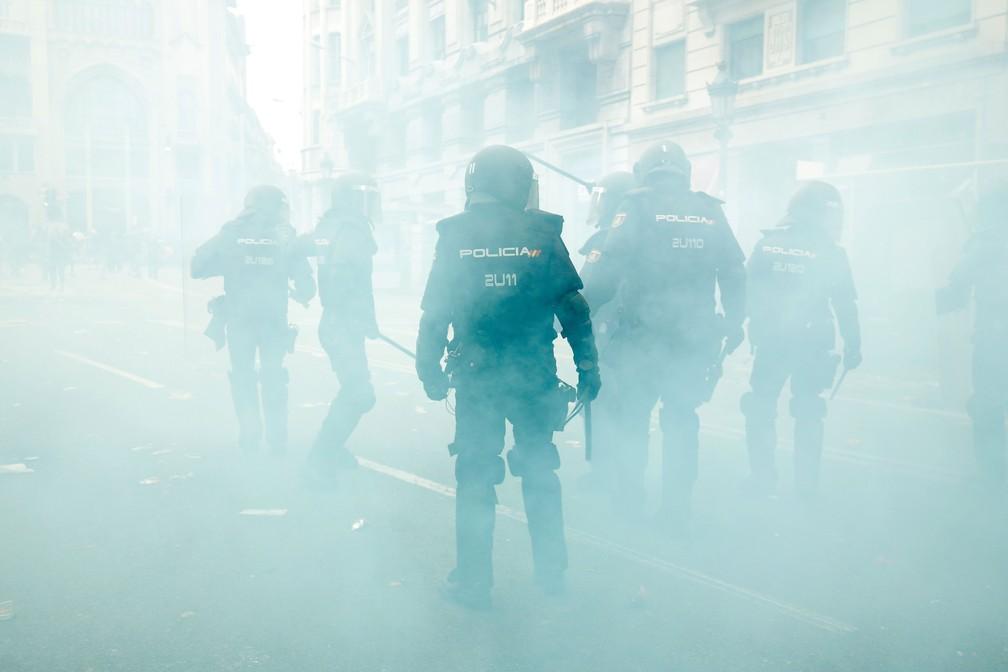 Policiais caminham no meio da fumaça enquanto protegem sede da polícia de Barcelona, nesta sexta-feira (18)  — Foto: Pau Barrena / AFP