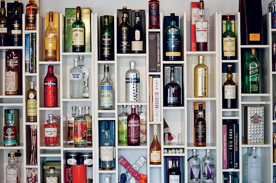 Uma estante com nichos de diversos tamanhos, inspirada em uma biblioteca de Nova York, guarda a coleção de bebidas do empresário Geraldo Mattar, apaixonado por gastronomia. As garrafas ficam ao lado de livros de receitas