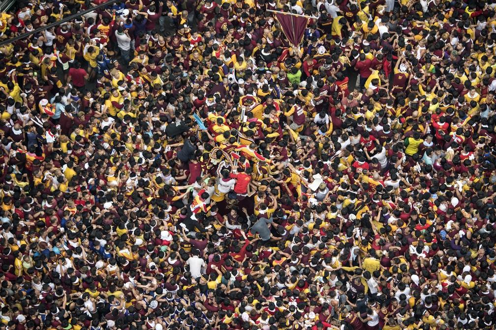 9 de janeiro - Devotos carregam a estátua do Nazareno Negro durante procissão religiosa em Manila, nas Filipinas. Centenas de milhares de peregrinos descalços juntaram-se ao desfile do Nazareno Negro, um ícone de ébano de Jesus Cristo carregando uma cruz, no maior festival religioso do país (Foto: Noel Celis/AFP)
