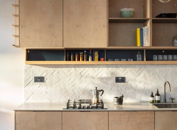 Entre as prateleiras da cozinha, encontra-se uma ilha móvel que pode ser deslocada para receber convidados (Foto: Ståle Eriksen/Reprodução)
