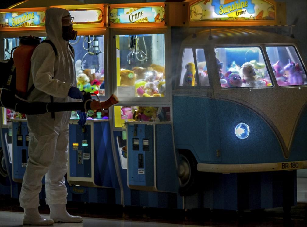 13 de maio - Funcionário com equipamento de proteção desinfeta shopping como medida preventiva contra o coronavírus (COVID-19), em Caxias do Sul — Foto: Silvio Avila/AFP