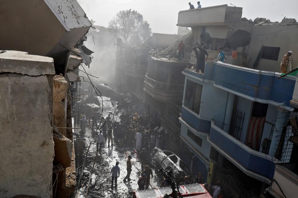 Bombeiros trabalham no resgate após avião comercial cair com cerca de 100 passageiros em área residencial perto do aerporto de Karachi, no Paquistão — Foto: Akhtar Soomro/Reuters