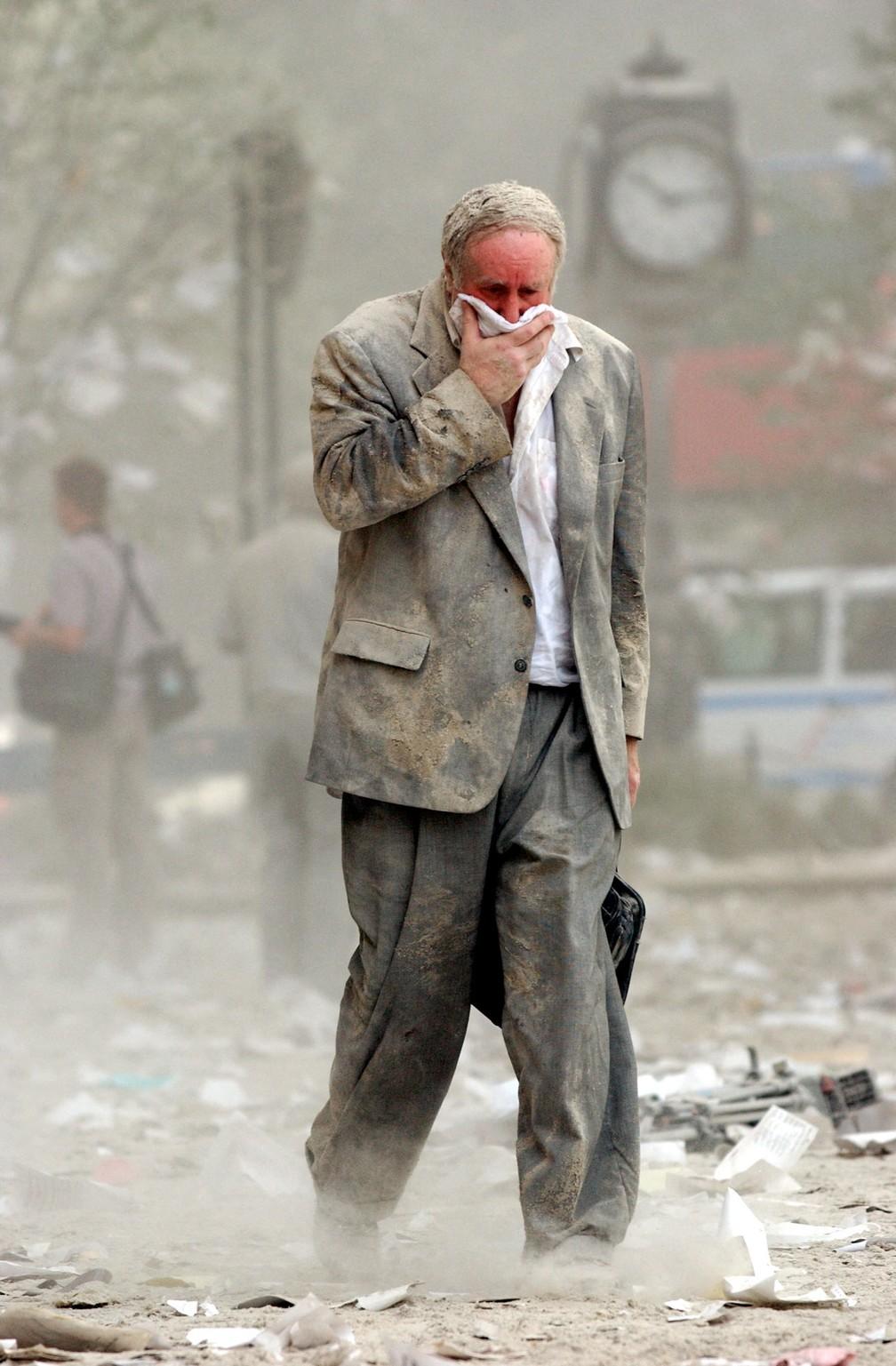 Sobrevivente do 11 de Setembro, Edward Fine cobre a boca enquanto caminha em meio a pó e destroços após a queda de uma das Torres Gêmeas em Nova York — Foto: Stan Honda/AFP/Arquivo