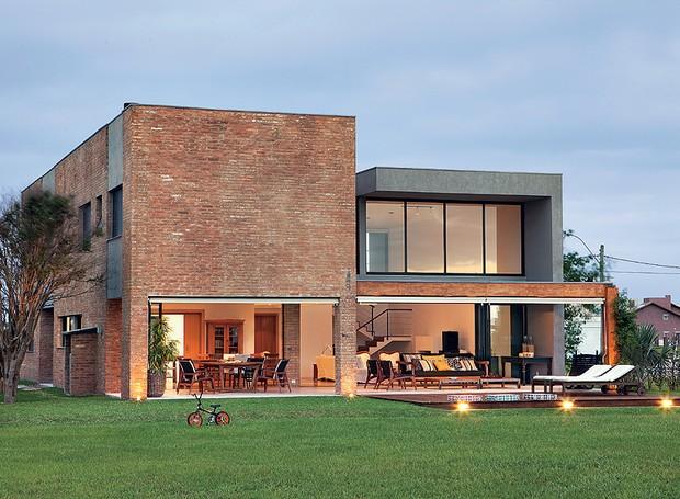 Tijolos de demolição revestem a fachada desta casa de 346 m², no litoral gaúcho. A boa ventilação e a iluminação natural são os trunfos do projeto do escritório Seferin (Foto: Edu Castello / Casa e Jardim)
