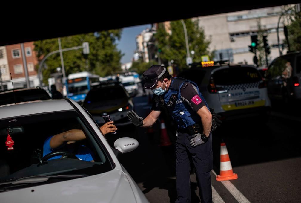 Motorista para em um posto de controle em Madri, na Espanha, nesta segunda-feira (21). Região está sob novas regras de restrição da circulação por causa do novo coronavírus  — Foto: Bernat Armangue/AP