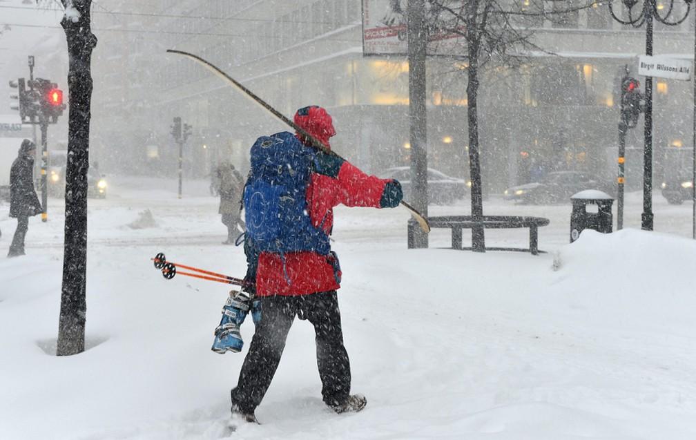 Homem carrega esqui pelas ruas cheias de neve em Estocolmo (Foto: Anders Wiklund/AP)