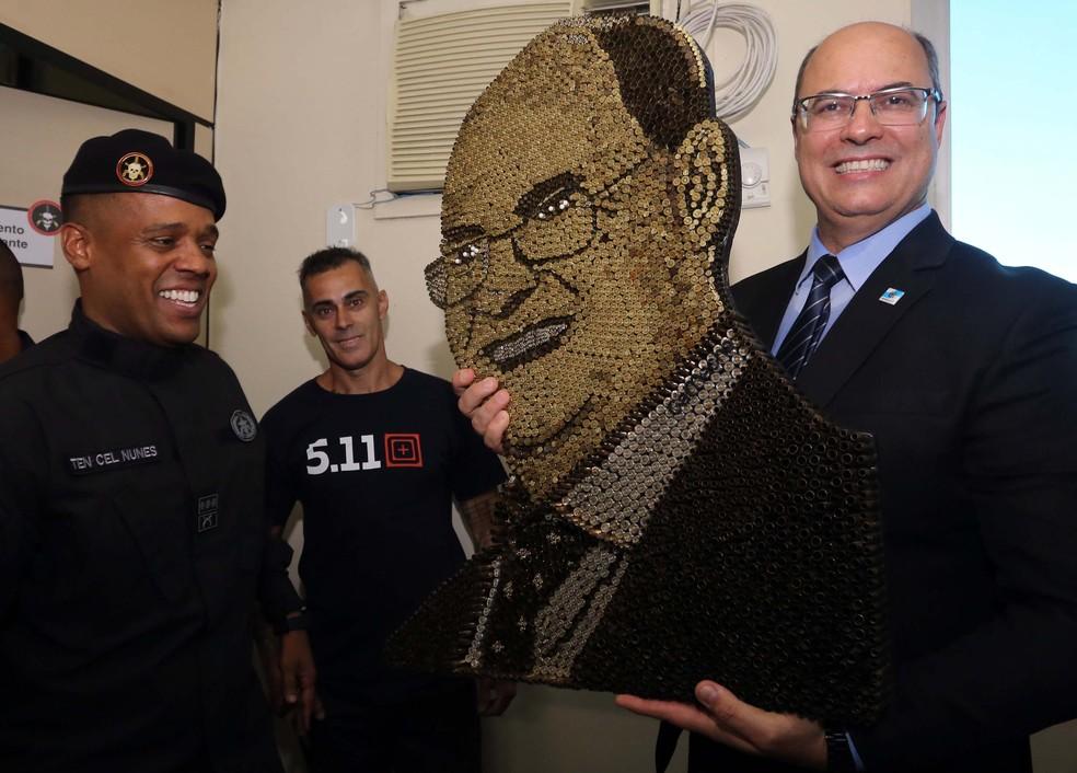 Wilson Witzel recebe de presente um quadro com seu rosto feito de projéteis — Foto: Carlos Magno/Governo do Rio de Janeiro