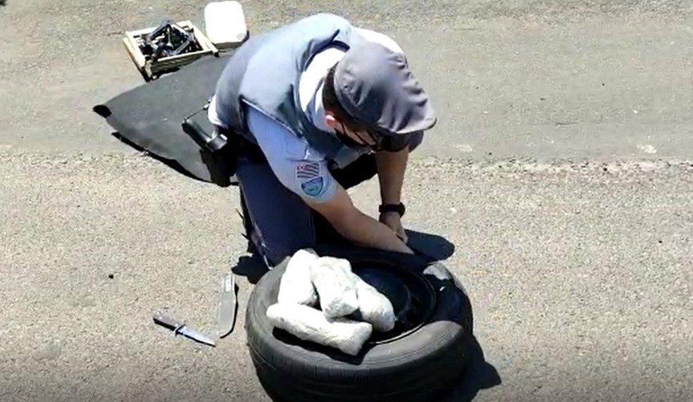 Policiais precisaram cortar o pneu do estepe com uma faca para retirar os pacotes da droga — Foto: Polícia Rodoviária/Divulgação