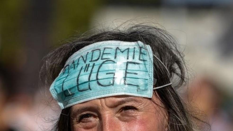 Manifestante em Berlim usa máscara que diz: 'Mentira da pandemia' — Foto: EPA/FELIPE TRUEBA