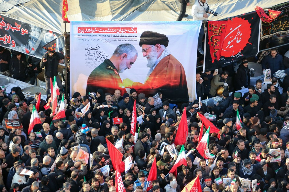 Cartaz com a foto do líder espiritual do Irã, aiatolá Ali Khamenei, concedendo a maior honra militar do país ao general Qasem Soleimani, morto em ataque americano, é visto durante funeral em Teerã, nesta segunda-feira (6) — Foto: Atta Kenare / AFP