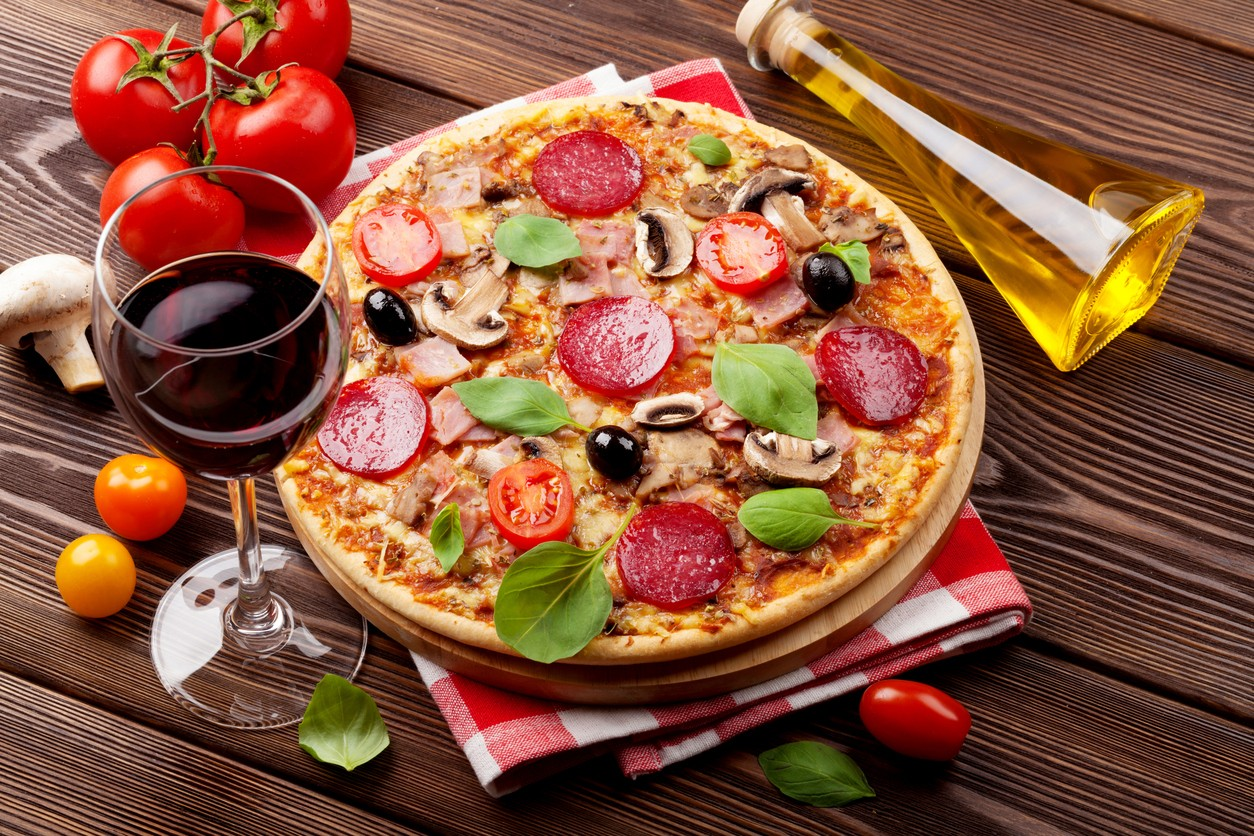 Italian pizza with pepperoni, tomatoes, olives, basil and red wine on wooden table. Top view (Foto: Getty Images/iStockphoto)