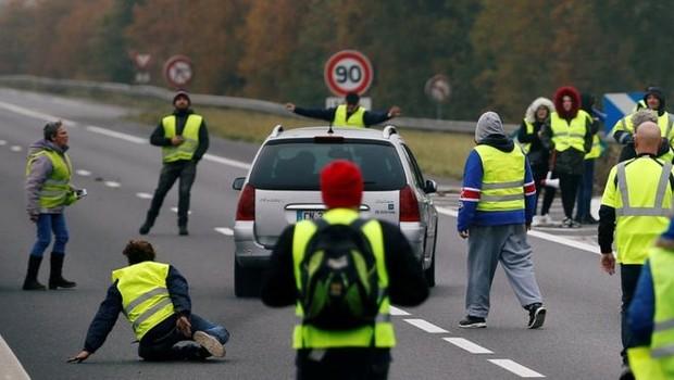 Um carro avança sobre um grupo de 'coletes amarelos', os manifestantes franceses que estão paralisando vias contra aumento do preço do diesel na França (Foto: Reuters/BBC)