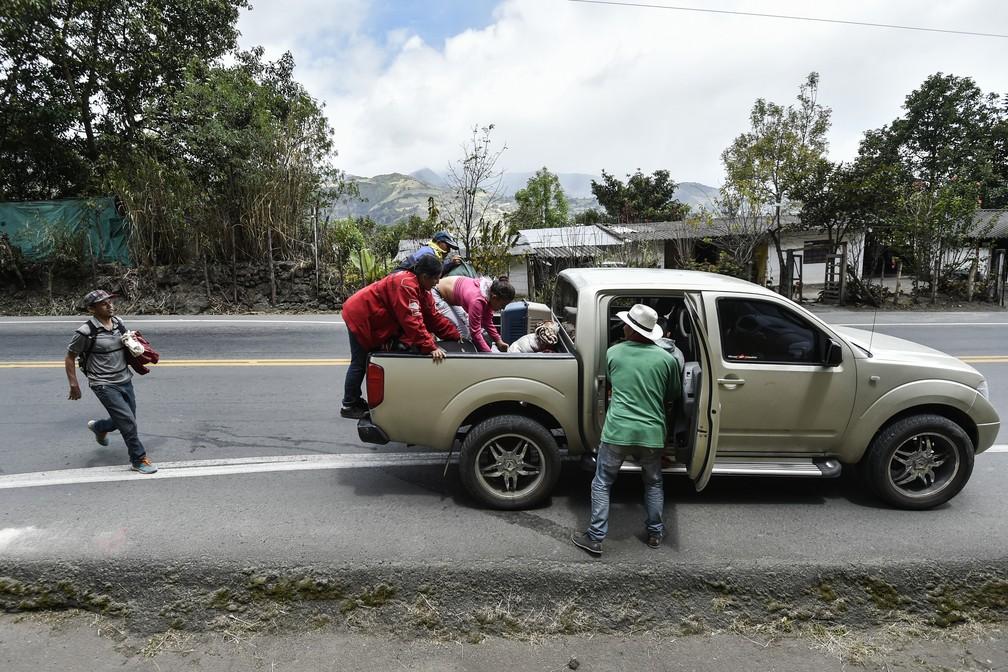 Venezuelanos embarcam em caminhonete em estrada da Colômbia, rumo ao Peru (Foto: Luis Robayo/ AFP)