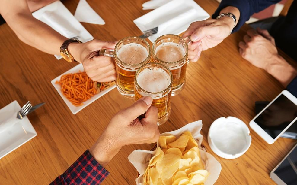 Pessoas brindam em bar — Foto: DragonImages