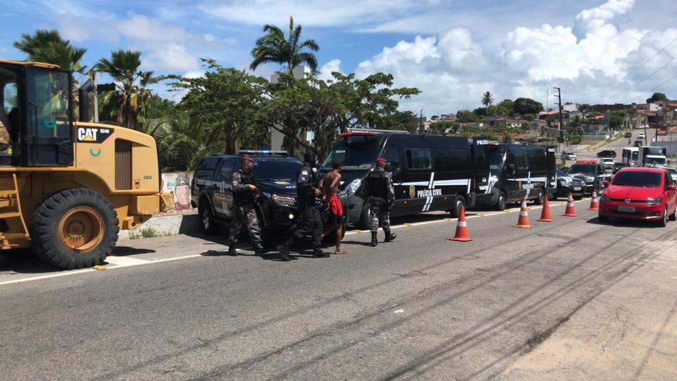 Homem é conduzido à unidade móvel da Polícia Civil durante Operação Concórdia no Passo da Pátria, Zona Leste de Natal. — Foto: Geraldo Jerônimo/Inter TV Cabugi