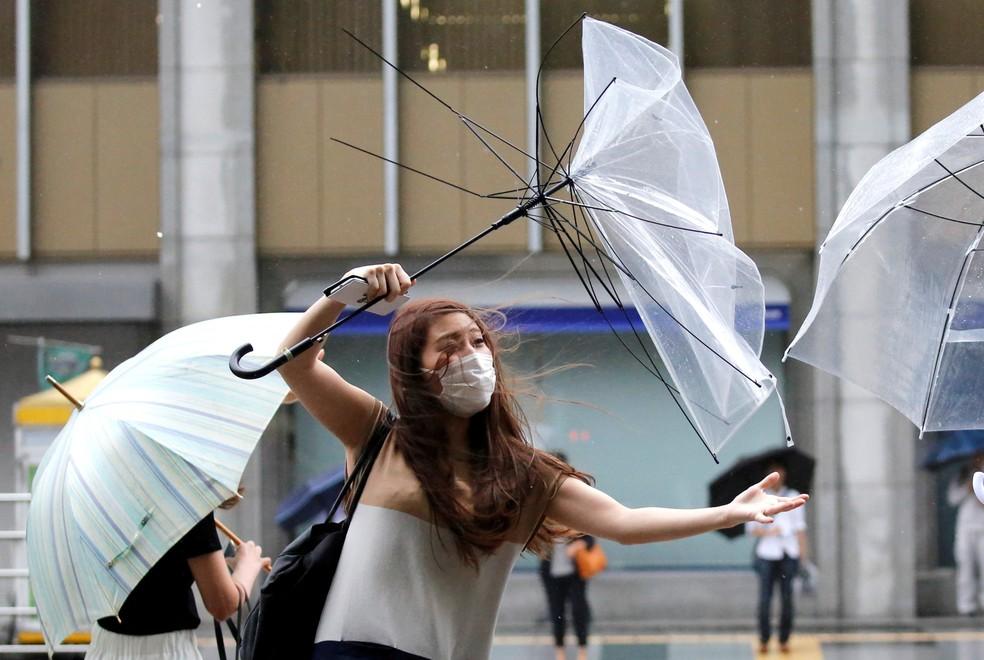 -  Uma mulher luta para manter seu guarda-chuva durante ventania nesta quarta-feira  8  com a aproximação do tufão Shanshan em Tóquio, no Japão  Foto: T