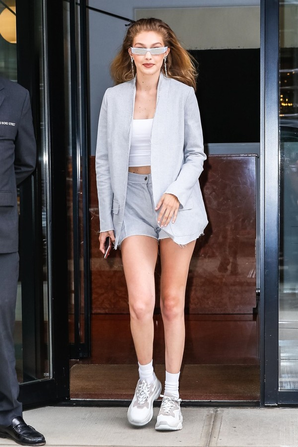 New York, NY  - A smiling Gigi Hadid shows off her toned abs and long legs in a white crop top and grey short shorts, topped with a grey jacket as she leaves her home for the afternoon. The supermodel has a lot to smile about, as she just recently took to (Foto: BACKGRID)