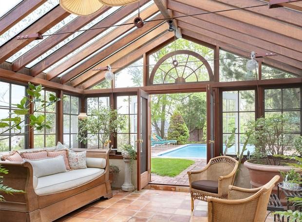 Para conectar a casa à área externa, uma construção em formato de estufa é possui sofás e poltronas rústicos e é iluminada pelo sol que passa pelas janelas francesas (Foto: Ellis Sotheby's International Realty/ Reprodução)