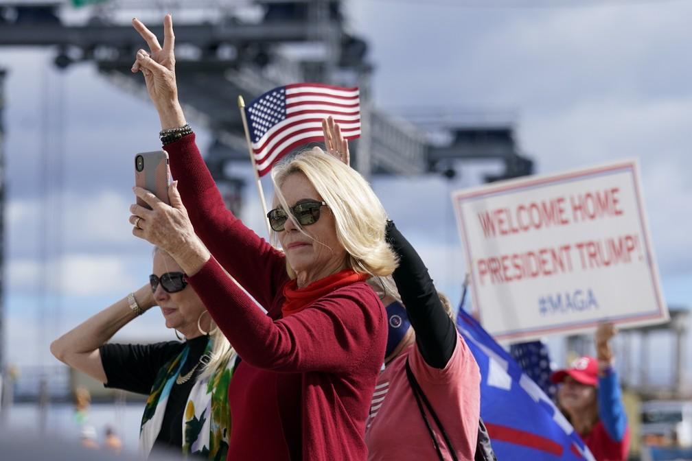 Apoiadores do presidente Donald Trump acenam enquanto a comitiva passa na estrada para Mar-a-Lago, propriedade de Trump em Palm Beach, na Flórida, nesta quarta-feira (20)   — Foto: Lynne Sladky/AP