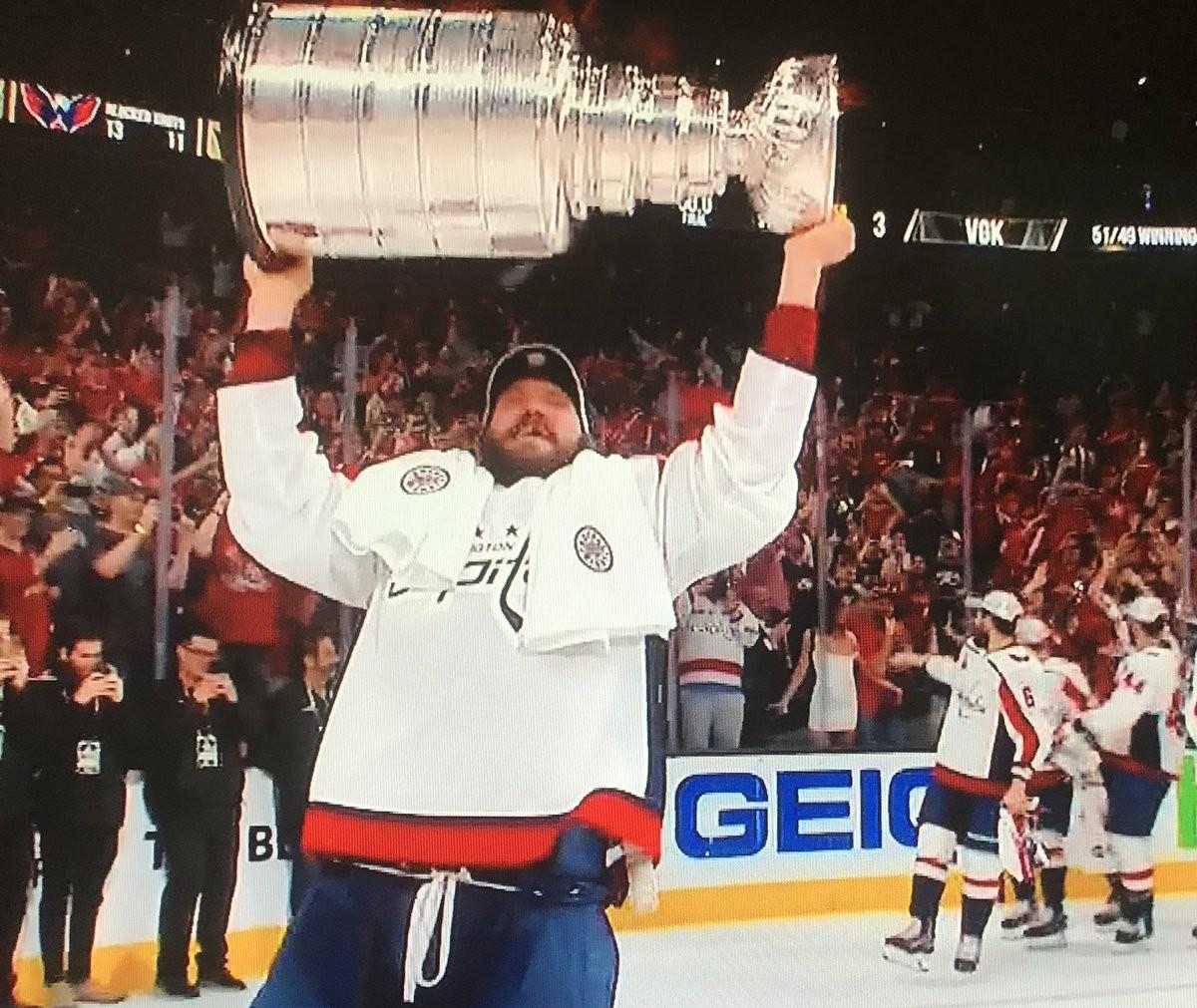 O capitão do Capitals com a taça da NHL enquanto seus colegas de equipe demonstram espanto com a celebração inesperada de uma torcedora (Foto: Reprodução)