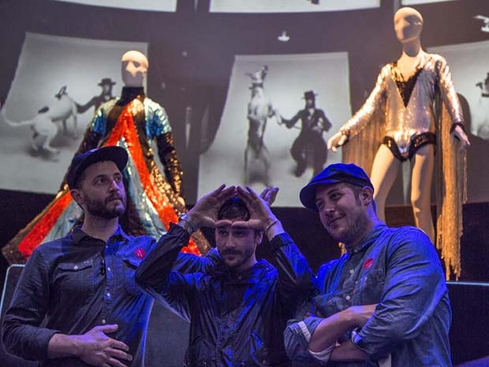 Integrantes do Portugal The Man posam ao lado de figurinos da exposição de David Bowie em SP — Foto: Divulgação/MIS