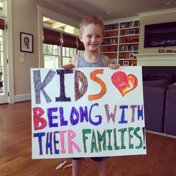 """Austin segurando uma placa em que está escrito em tradução livre: """"O lugar das crianças é com as famílias delas"""" (Foto: Arquivo pessoal)"""
