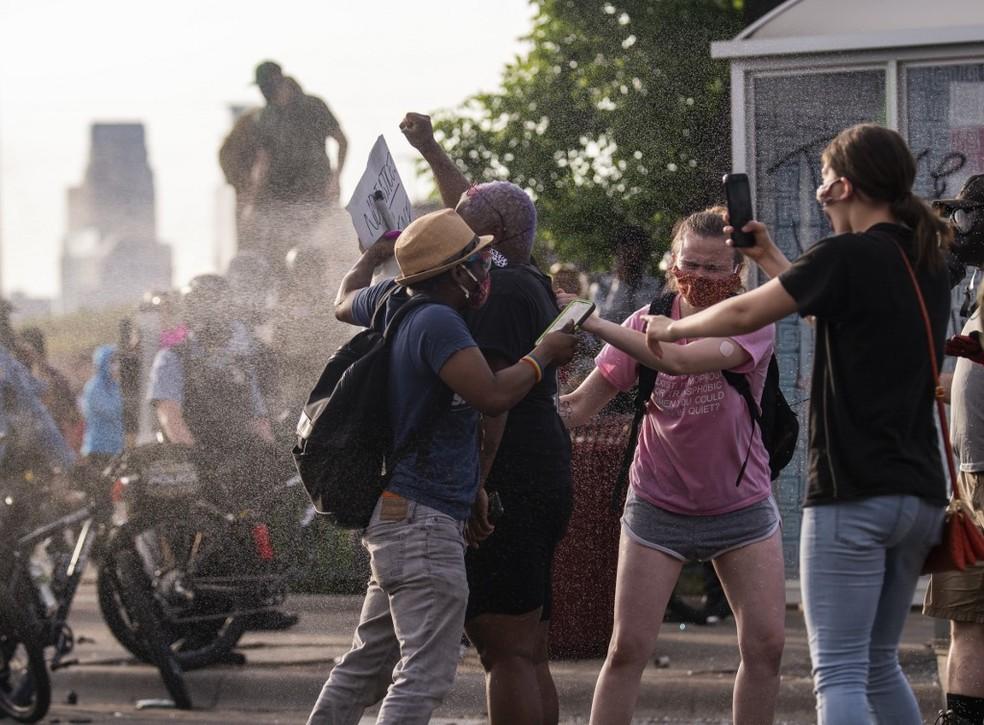 Manifestantes reagem a spray de pimenta em Minneapolis — Foto: Stephen Maturen / Getty Images/ Via AFP