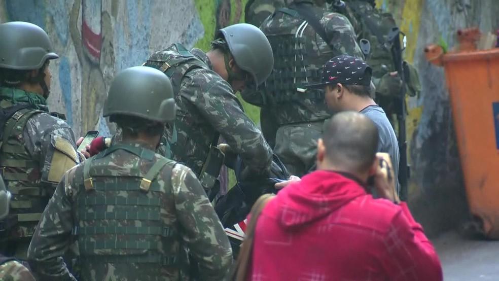 Policiais revistam moradores na saída de comunidade na Zona Sul (Foto: Andressa Gonçalves/ G1)