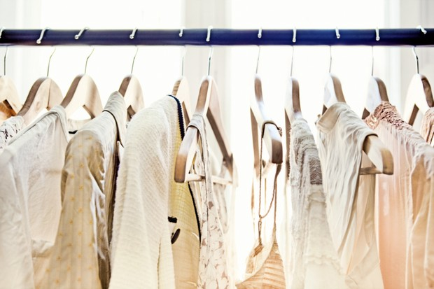 A row of light-colored clothing secured on wooden hangers is visible from about armpit level up, dangling from a rod which stretches from one end of the frame to the other.  Behind the rack, two large windows brighten the room with daylight. (Foto: Getty Images)