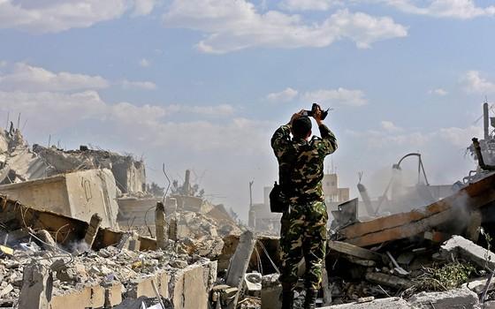 Um soldado sírio inspeciona os danos a edifício que abrigaria centro de pesquisas no norte de Damasco (Foto: LOUAI BESHARA/AFP)