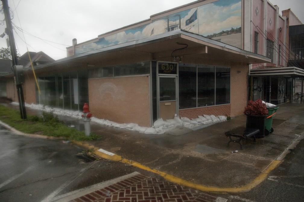 Sacos de areia são colocados em porta de de loja em Louisiana antes de chegada de tempestade tropical Barry — Foto: Seth HERALD / AFP