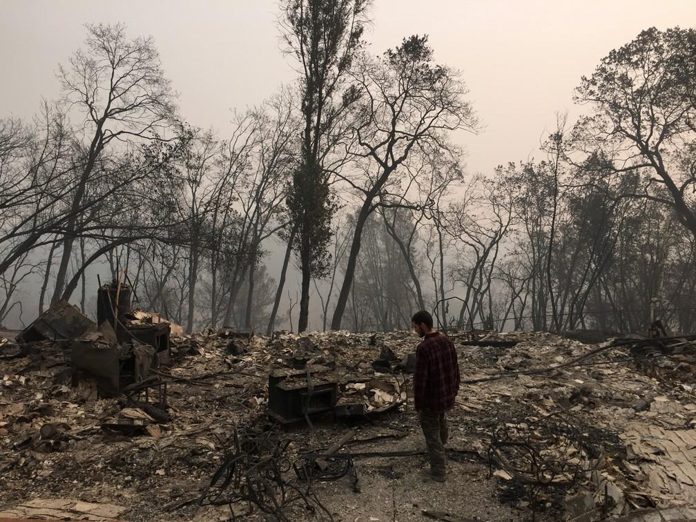 Jhonathan Clark caminha onde era sua casa, destruída pelo incêndio florestal conhecido localmente como 'Camp Fire', em Paradise, na Califórnia — Foto: Javier Tovar/AFP