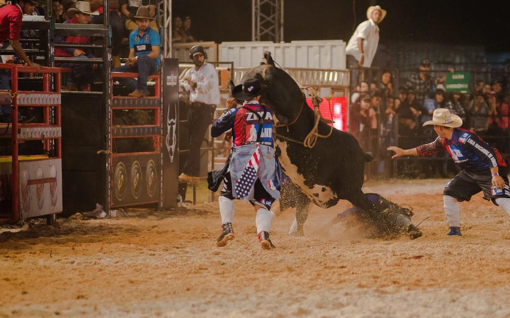 Salva-vidas tentam atrair atenção do touro para tirar peão debaixo do animal no Ribeirão Rodeo Music 2018 (Foto: Érico Andrade/G1)