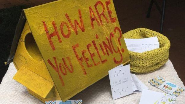 """Caixa com a pergunta """"como você está se sentindo?"""", uma estratégia para começar conversas sobre saúde mental no Zimbábue (Foto: The Friendship Bench Zimbabwe/BBC)"""