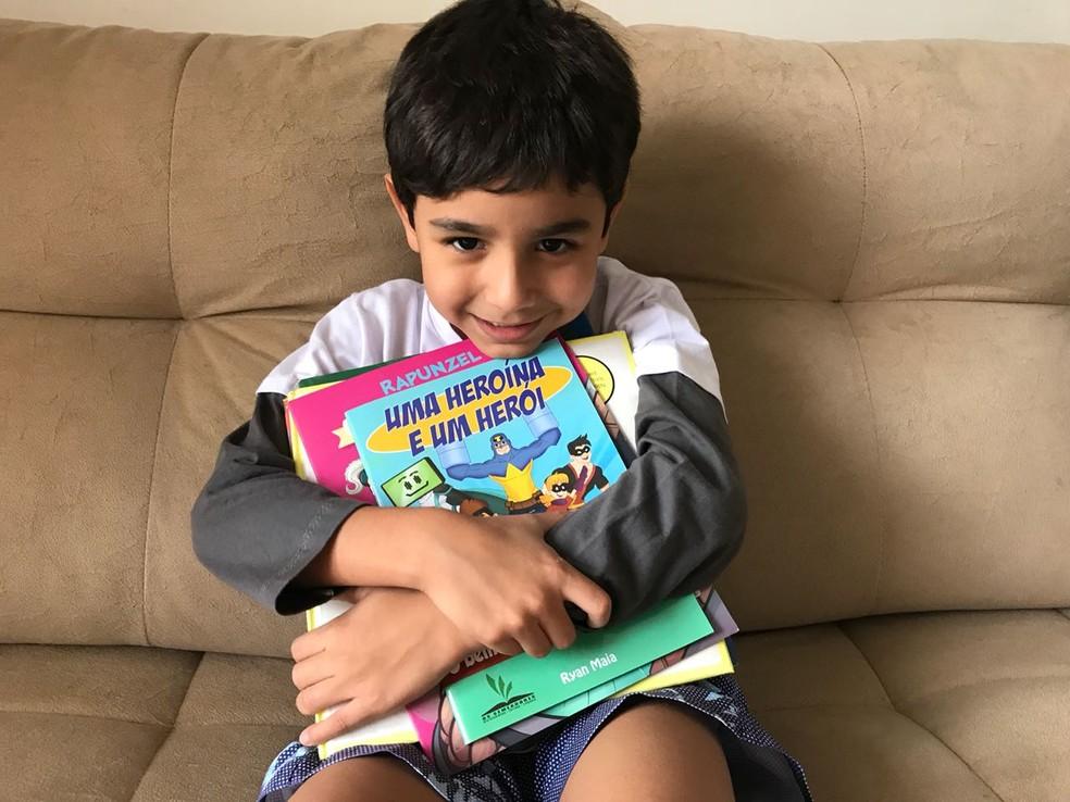 Ryan Maia, 7 anos, abraça os livros prediletos; entre eles, o de sua autoria, 'uma heroína e uma herói' — Foto: Marília Marques/G1