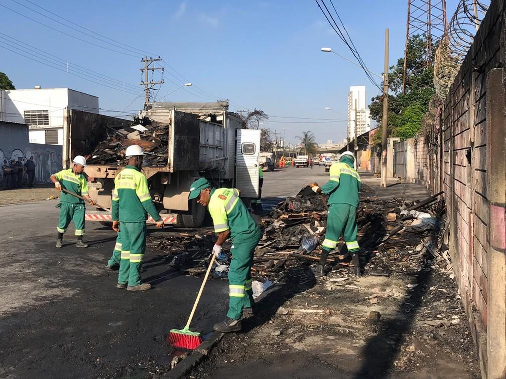 Funcionários da Prefeitura limpam resíduos e retiram entulhos deixados por moradores da Favela do Cimento após reintegração de posse — Foto: Adriano Marques/G1
