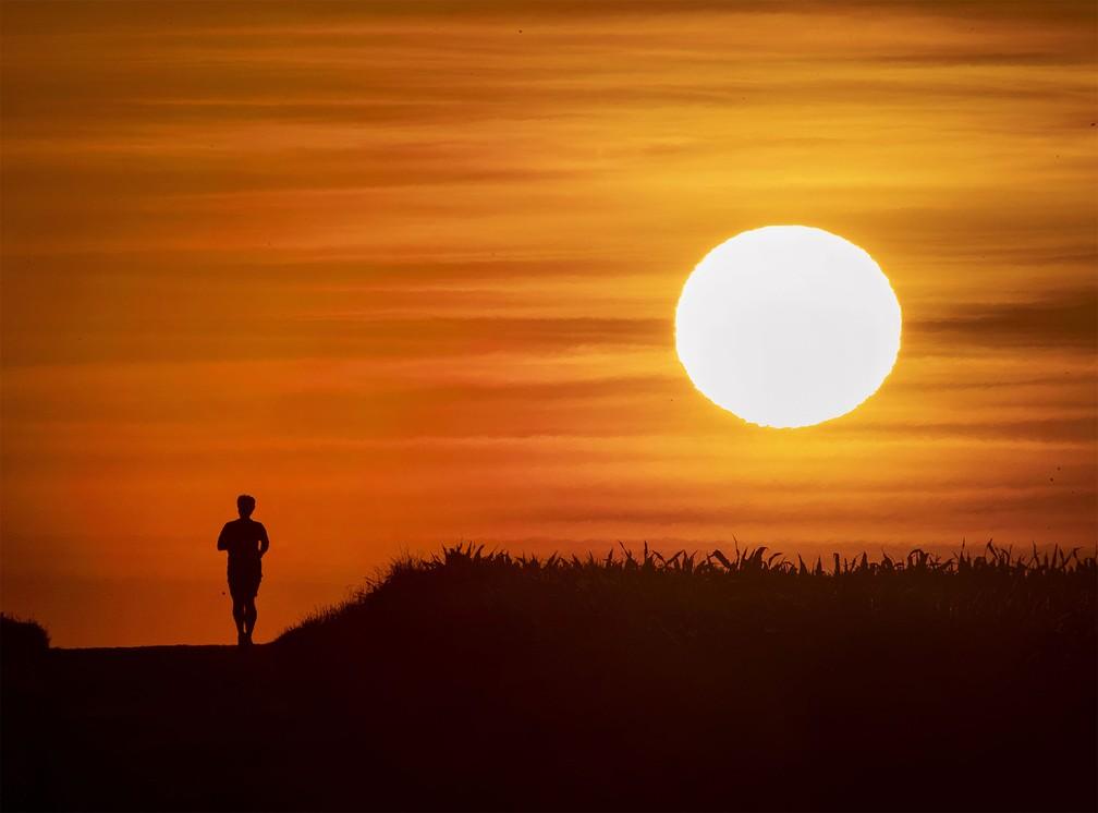 25 de junho - Homem pratica corrida durante o amanhecer em uma via de Frankfurt, na Alemanha — Foto: Michael Probst/AP