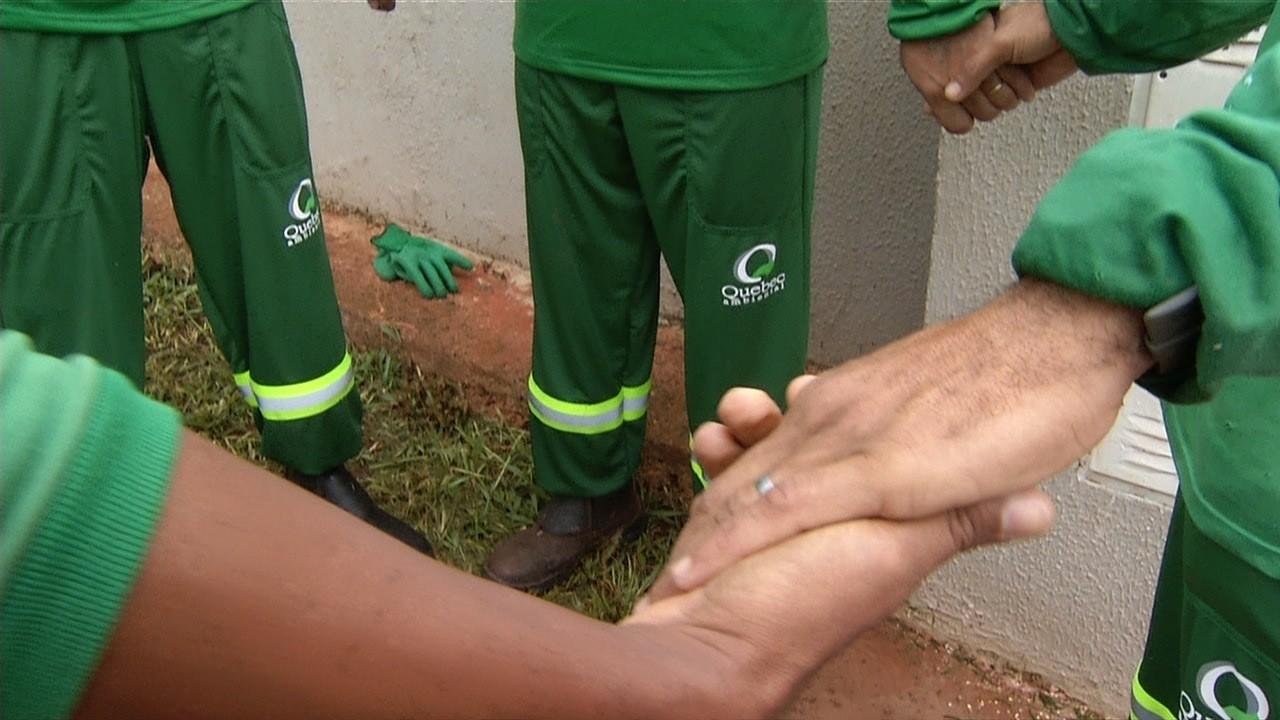Coletores de lixo são fotografados fazendo oração antes do trabalho em Valparaíso de Goiás