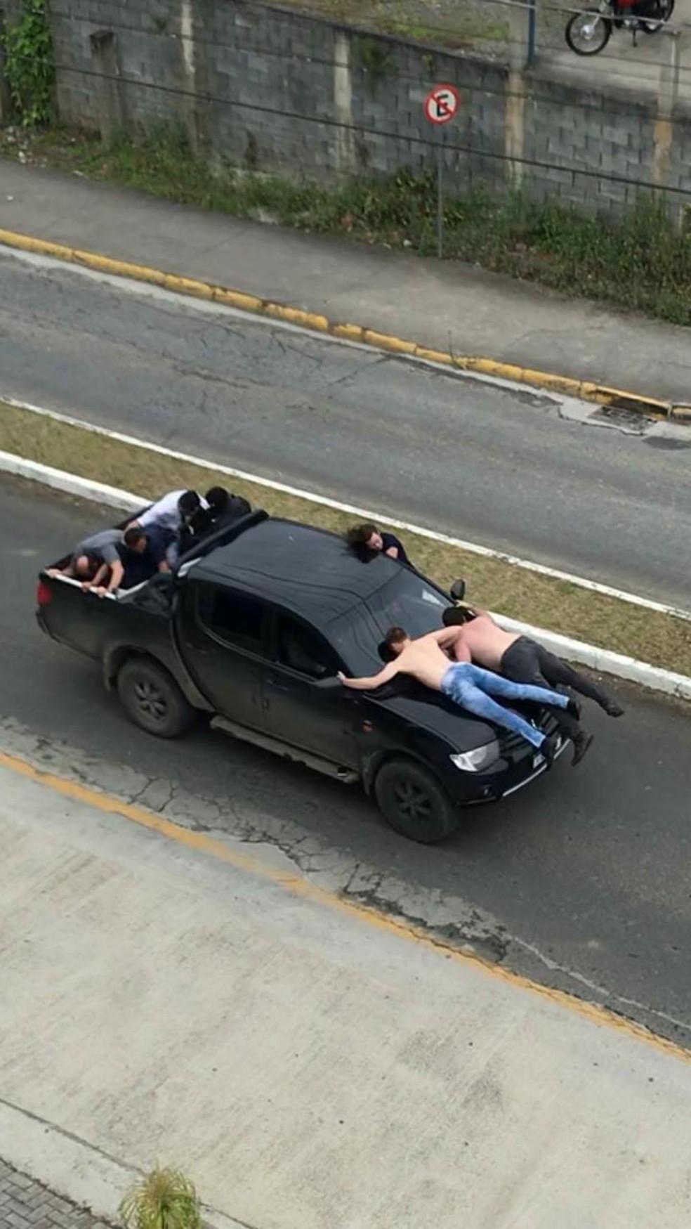 Reféns sobre o capô da caminhonete utilizada na fuga dos criminosos  — Foto: Reprodução/ NSC TV